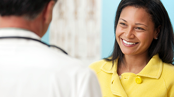 woman in yellow smiling at dentist