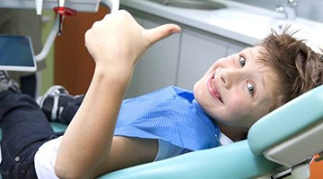 Young boy in dental chair giving thumbs up