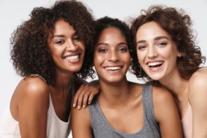 Three women standing close together smiling